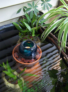 Small outdoor water garden with flameless candle