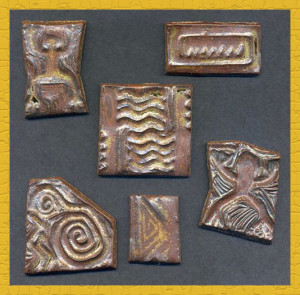 Handmade stoneware tiles impressed with carved rubber stamps. These will be installed in tile murals in my kitchen.